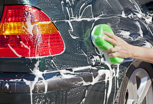 Closeup image of a hand with a soapy sponge washing a vehicle