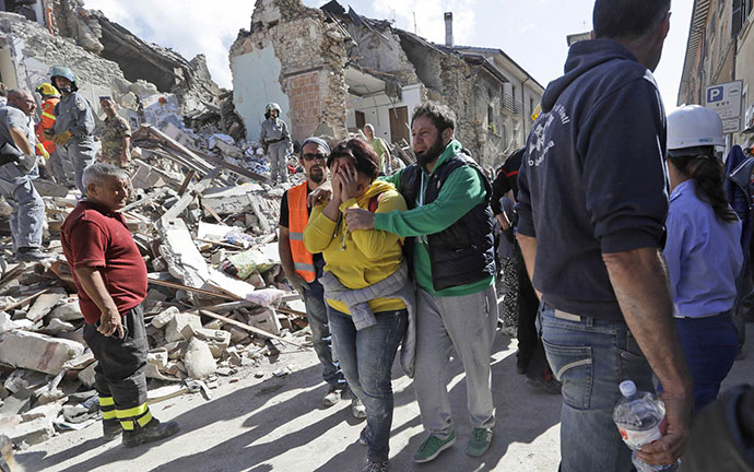 A woman is comforted as she walks through rubble after an earthquake, in Amatrice, central Italy, Wednesday, Aug. 24, 2016. A devastating earthquake rocked central Italy early Wednesday, collapsing homes on top of residents as they slept. At least 23 people were reported dead in three hard-hit towns where rescue crews raced to dig survivors out of the rubble, but the toll was expected to rise as crews reached homes in more remote hamlets. (AP Photo/Alessandra Tarantino)